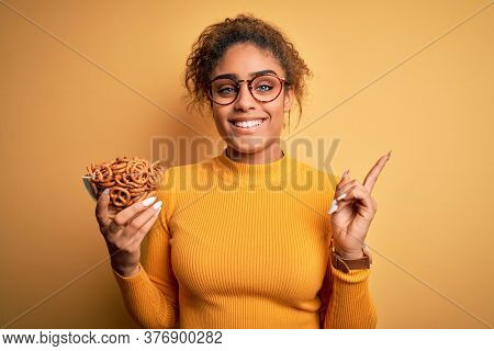 African american afro girl holding bowl with german baked pretzels over yellow background very happy pointing with hand and finger to the side