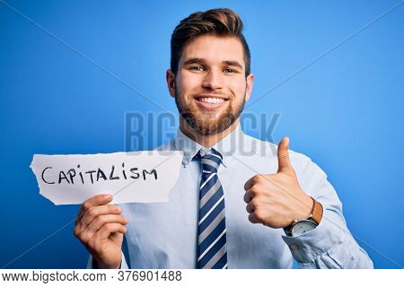 Young blond businessman with beard and blue eyes holding paper with capitalism message happy with big smile doing ok sign, thumb up with fingers, excellent sign