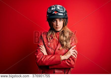 Young beautiful brunette motrocyclist woman wearing moto helmet over red background skeptic and nervous, disapproving expression on face with crossed arms. Negative person.