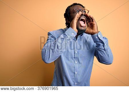 Young handsome african american man wearing shirt and glasses over yellow background Shouting angry out loud with hands over mouth