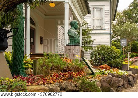 Nagasaki, Japan, 03/11/2019. Colonial Style White Wooden Building, Autumn Flowers And Man's Statue I