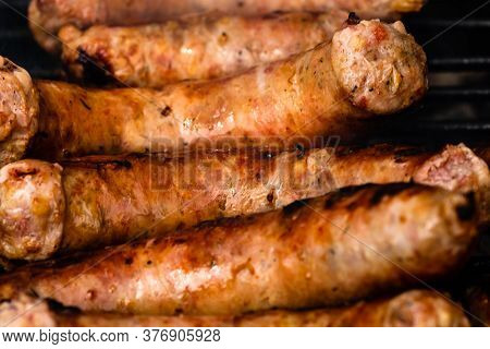 Close Up On Details Of Homemade Sausages On Barbecue Grill. Barbecue, Grill And Food Concept.