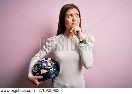 Young beautiful motorcyclist woman with blue eyes holding moto helmet over pink background serious face thinking about question, very confused idea