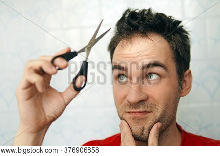 Fear Of Cutting Hair. Young Man Cutting His Own Hair Using Scissors During Quarantine From Covid 19