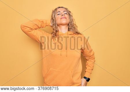 Young beautiful blonde sporty woman wearing casual sweatshirt over yellow background Suffering of neck ache injury, touching neck with hand, muscular pain