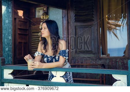 Young Woman In Blue Dress Sitting On A Porch Or Veranda Of Wooden Summer Cottage Or Bungalow And Dri