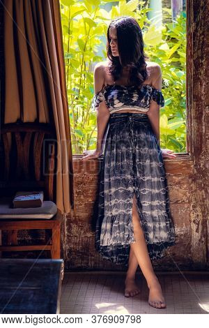 Young Woman Sitting By The Window Of Wooden Summer Cottage Or Bungalow. Eco Lifestyle Concept. Tropi