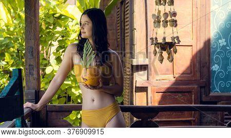 Young Tan Beautiful Woman In Yellow Bikini Relaxing In Tropical Rustic Bungalow With Young Coconut D