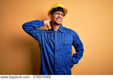 Young handsome african american worker man wearing blue uniform and security helmet Suffering of neck ache injury, touching neck with hand, muscular pain