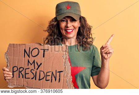 Middle age brunette communist woman holding banner with not my president message smiling happy pointing with hand and finger to the side