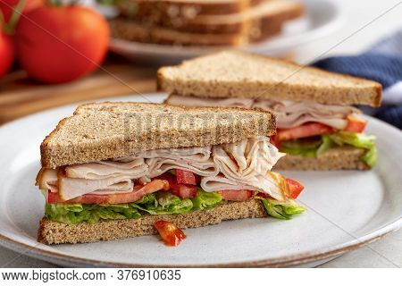 Healthy Sandwich With Turkey, Tomato And Lettuce On Whole Wheat Bread On A White Plate