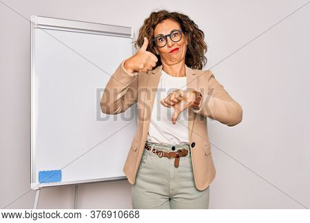 Middle age senior business woman standing on seminar presentation by magnectic blackboard Doing thumbs up and down, disagreement and agreement expression. Crazy conflict