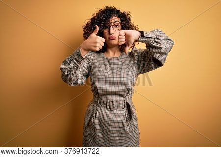 Beautiful arab business woman wearing dress and glasses standing over yellow background Doing thumbs up and down, disagreement and agreement expression. Crazy conflict