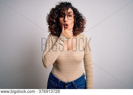 Young beautiful curly arab woman wearing casual t-shirt and glasses over white background Looking fascinated with disbelief, surprise and amazed expression with hands on chin