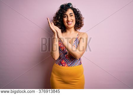 Young beautiful arab woman on vacation wearing swimsuit and sunglasses over pink background clapping and applauding happy and joyful, smiling proud hands together