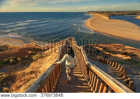 Woman Walking Down Iconic Port Noarlunga Boardwalk While Watching Spectacular Sunset View, South Aus