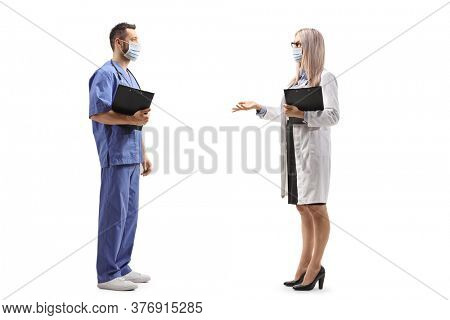 Full length profile shot of a female doctor and a male nurse talking and wearing face masks isolated on white background