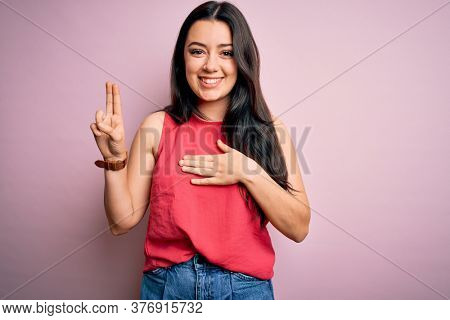 Young brunette woman wearing casual summer shirt over pink isolated background smiling swearing with hand on chest and fingers up, making a loyalty promise oath
