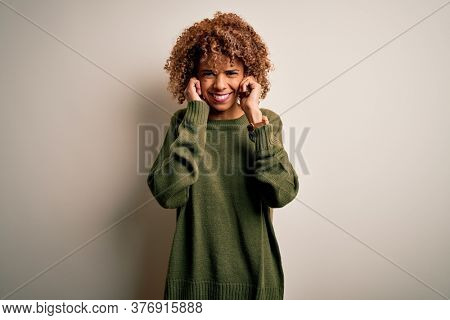 Beautiful african american woman with curly hair wearing casual sweater over white background covering ears with fingers with annoyed expression for the noise of loud music. Deaf concept.