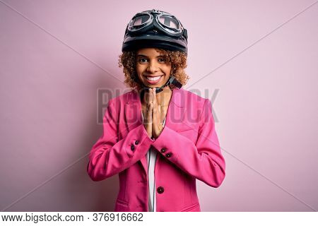 African american motorcyclist woman with curly hair wearing moto helmet over pink background praying with hands together asking for forgiveness smiling confident.