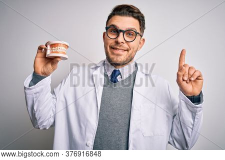 Young dentist man with blue eyes holding orthodontic dental prosthesis over isolated background surprised with an idea or question pointing finger with happy face, number one