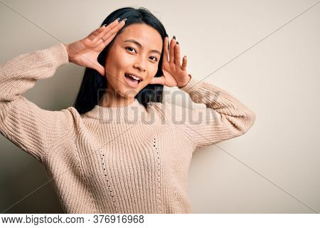 Young beautiful chinese woman wearing casual sweater over isolated white background Smiling cheerful playing peek a boo with hands showing face. Surprised and exited