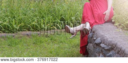 A Woman In A Red Dress Sits On A Rock In The Garden, Beautiful Feet And Shoes, Summer