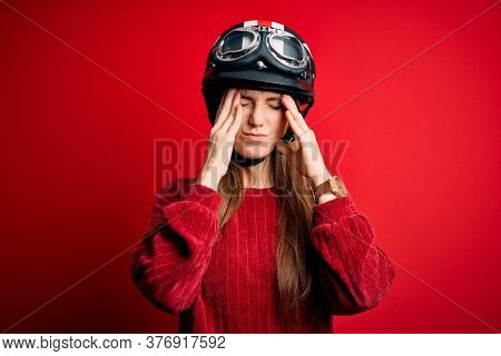 Young beautiful redhead motorcyclist woman wearing moto helmet over red background suffering from headache desperate and stressed because pain and migraine. Hands on head.