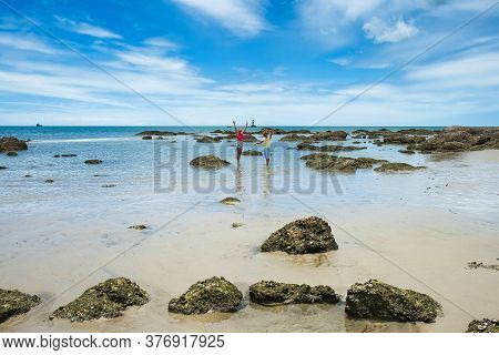 Two Caucasian Children, Brother And Sister, Walking On Wild Rocky Tropical Beach During Low Tide And