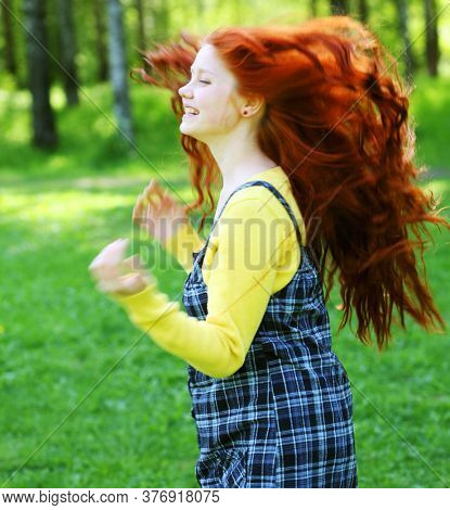 Portrait of beautiful smiling redhaired girl, outdoors