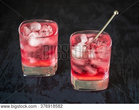 Cherry Carbonated Drink With Ice Cubes In Two Square Glass Glasses