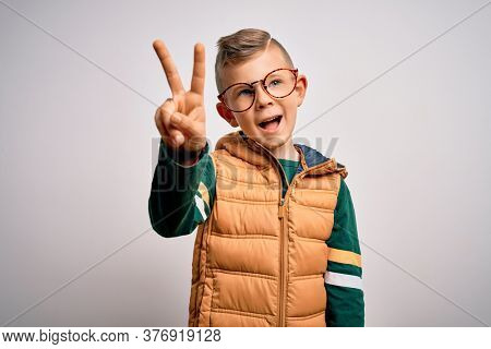 Young little caucasian kid with blue eyes wearing winter coat and smart glasses showing and pointing up with fingers number two while smiling confident and happy.