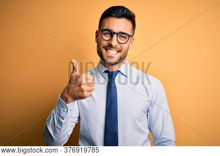 Young handsome businessman wearing tie and glasses standing over yellow background doing happy thumbs up gesture with hand. Approving expression looking at the camera showing success.