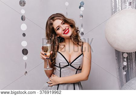Against Backdrop Of Bright Christmas Balls, Of Enormous Size, Very Beautiful Girl With Glass Of Spar