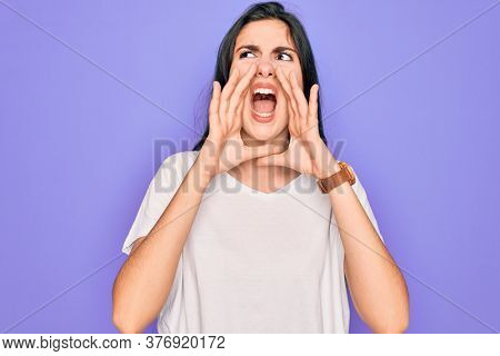 Young beautiful brunette woman wearing casual white t-shirt over purple background Shouting angry out loud with hands over mouth