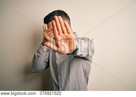 Young handsome man wearing elegant shirt and glasses over isolated white background covering eyes with hands and doing stop gesture with sad and fear expression. Embarrassed and negative concept.