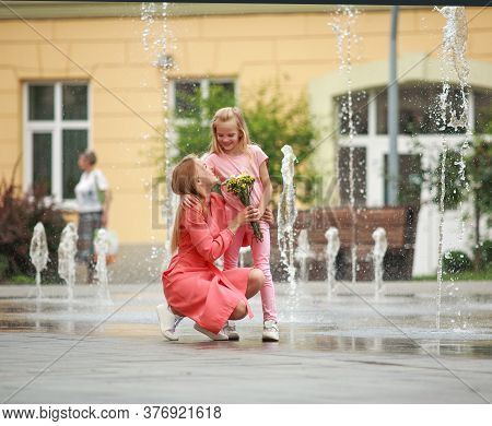 Mother And Daughter Have Fun Together At The Fountain In The Town Square