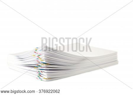 Colorful Paper Clip With Pile Of Overload White Paperwork Isolated On White. Top View