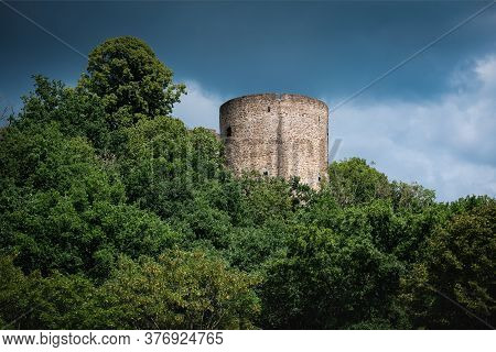 An Old Defense Tower On A Hill Protrudes From The Forest.