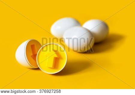 Plastic Eggs With Arrow Form On Yellow Background. An Educational Sorter Toy To Recognize And Match