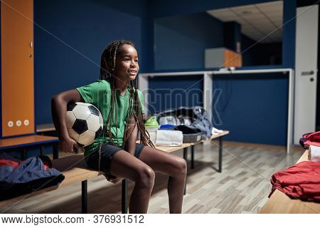 Soccer player preparing for game in locker room.Child girl with soccer ball in changing room.