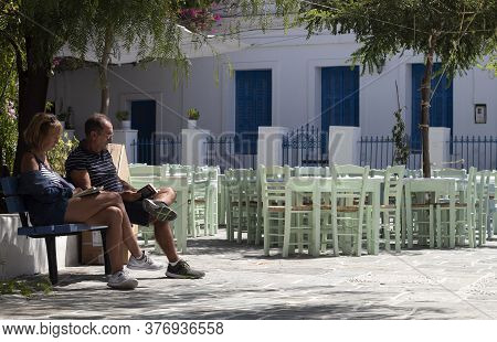 Folegandros, Cyclades / Greece / September 16 2019 : Late Afternoon In A Sunlit Square.  Two Tourist