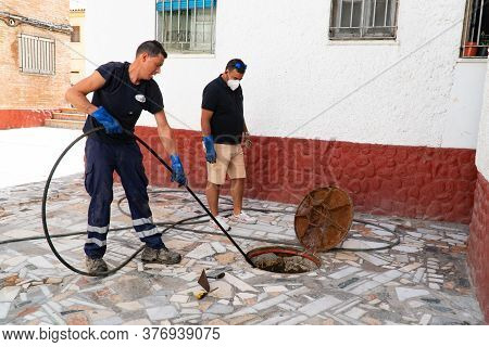 July 13, 2020. Granada. Spain: Workers Cleans The Drains Hatch And Removes Dirt And Debris From The