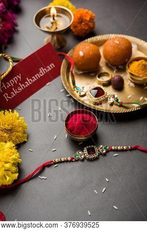 Indian Festival Raksha Bandhan With Rakhi Bracelets, Presents, Rice And Kumkum And Sweets In Plate