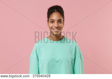Smiling Young African American Woman Girl In Green Sweatshirt Posing Isolated On Pastel Pink Backgro