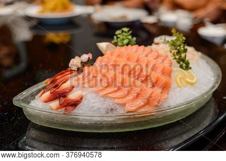 Fresh Salmon Sashimi, Lemon Slices And Greenery On Ice