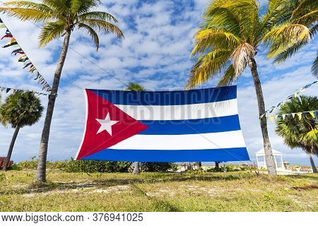 Cuban Flag Among Palm Trees. Cuban Flag Against Tropical Palm Trees And Blue Sky. Beautiful Tropical