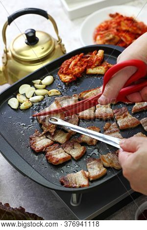 cooked samgyeopsal ( grilled pork belly BBQ ), being cut with scissors