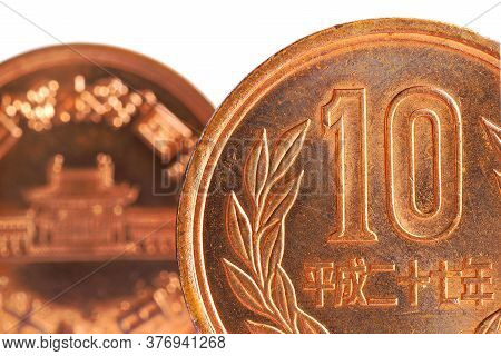 Japanese Ten Yen Coins On Both Sides Stand On A White Background. Fragments Of Close-up. Not Isolate