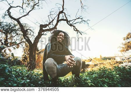 A Cheerful Guinean Black Girl With Curly Hair Is Squatting And Looking At The Camera In A Shadow Of